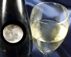 A glass of white wine with the moon reflecting in a wine bottle