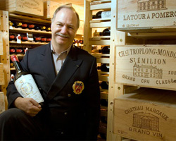 Eric Vogt, eProvenance's founder, stands in a wine cellar with a bottle of Bordeaux