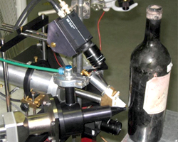 A particle accelerator authenticating the glass of a vintage wine bottle