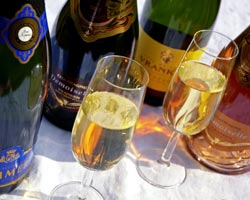Two glasses of Champagne surrounded by bottles of the sparkling wine
